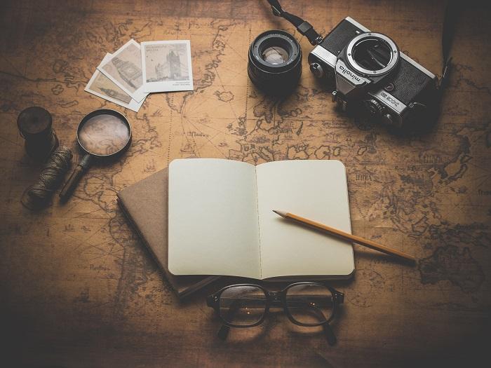 Mapa del mundo con cámara de fotos, lupa, libro, gafas